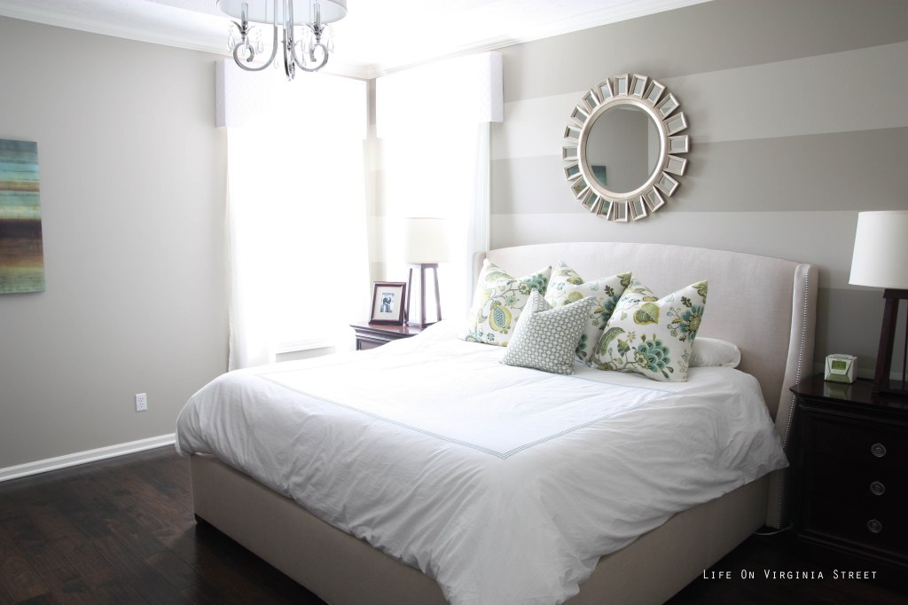 Striped neutral walls and designer master bedroom pillows