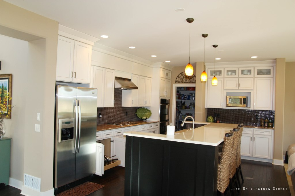 View of a kitchen with an island and lights above the island.